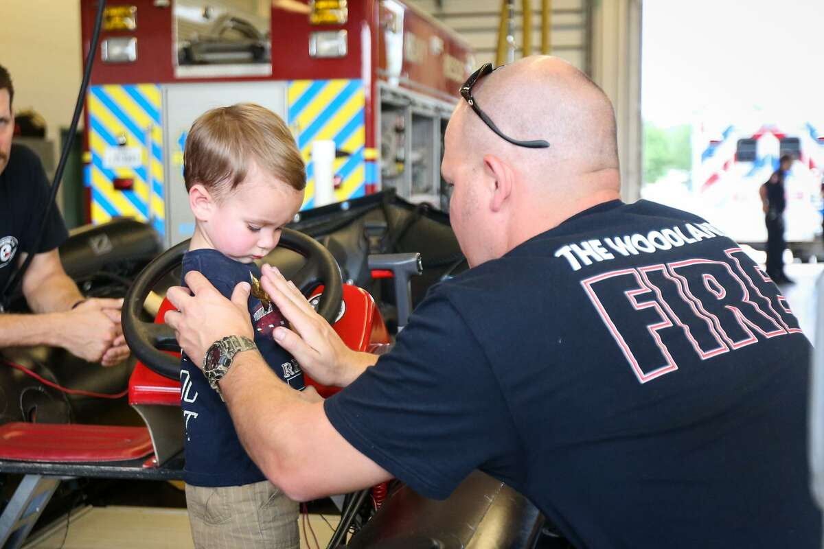 At some point this summer, each fire station in The Woodlands will roll up their garage doors for community members to come and see their public safety equipment in a series of open houses. Here, The Woodlands firefighter Jimmy Ballinger, right, places a sticker badge on James Ramsay, 2, during the open house on Saturday, July 15, 2017, at The Woodlands Fire Station #6.