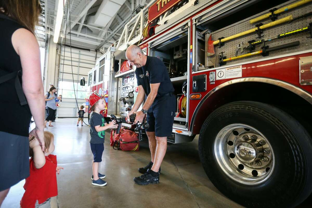 At some point this summer, each fire station in The Woodlands will roll up their garage doors for community members to come and see their public safety equipment in a series of open houses. Here, Driver/operator Gerard van der Werff, of The Woodlands Fire Department, right, lets Tucker Flowers, 3, hold various pieces of fire engine equipment during the open house on Saturday, July 15, 2017, at The Woodlands Fire Station #6.
