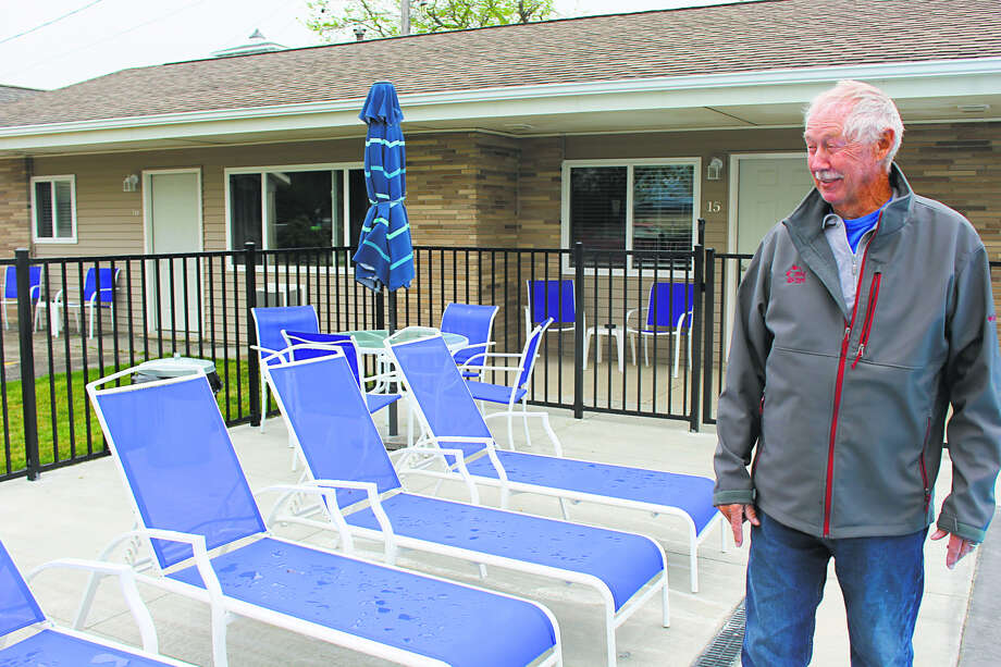 Gary Babcock shows off pool furniture at the Beachcomber Motel in Port Austin. The motel recently finished a number of renovations. (Robert Creenan/Huron Daily Tribune)