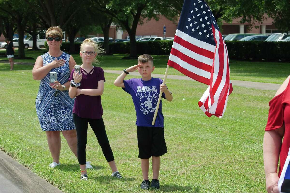 Pam Daley, Jalynn Myers and Grayson Myers show their respects as a procession for Kemah Police Chief Chris Reed passes south on FM 270 Friday, June 14.