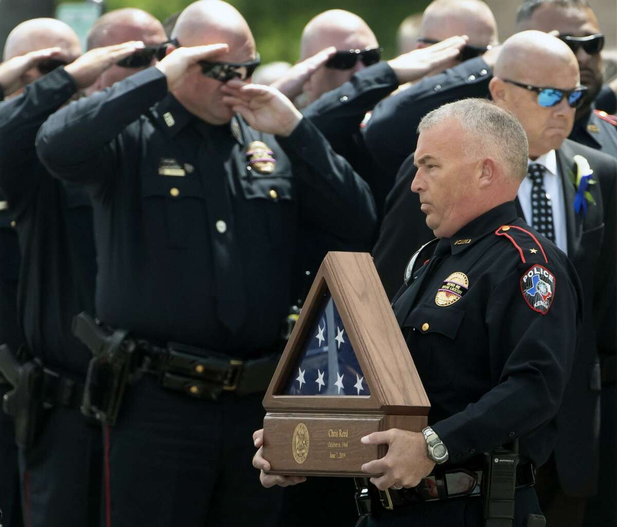 Kemah Police officers salute as a framed U.S. flag and an urn bearing the ashes of Kemah Police Chief Chris Reed are carried from Clear Creek Community Church following a memorial service in League City, Texas on Friday, June 14, 2019. Kemah Police officers salute as a framed U.S. flag and an urn bearing the ashes of Kemah Police Chief Chris Reed are carried from Clear Creek Community Church following a memorial service in League City, Texas on Friday, June 14, 2019. The 50-year-old police chief was thrown overboard without a life jacket when a wave from a large passing vessel struck his boat.