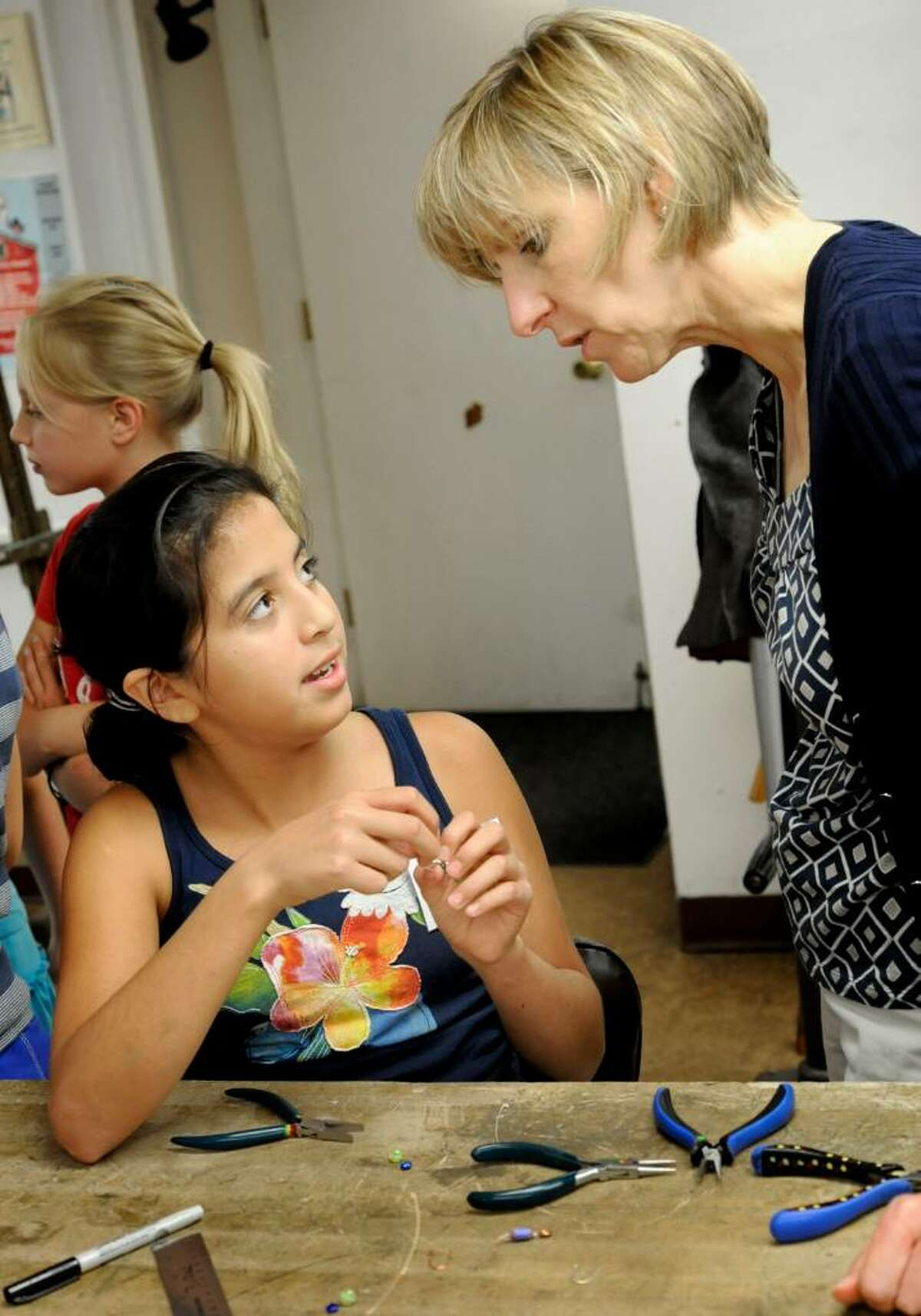 Volunteer Katee Sosa, 11,explains earring making to Barbara Stauder, 54, of Danbury, during the Brookfield Craft Center's Open House '09 on Sunday, Sept. 6, 2009.