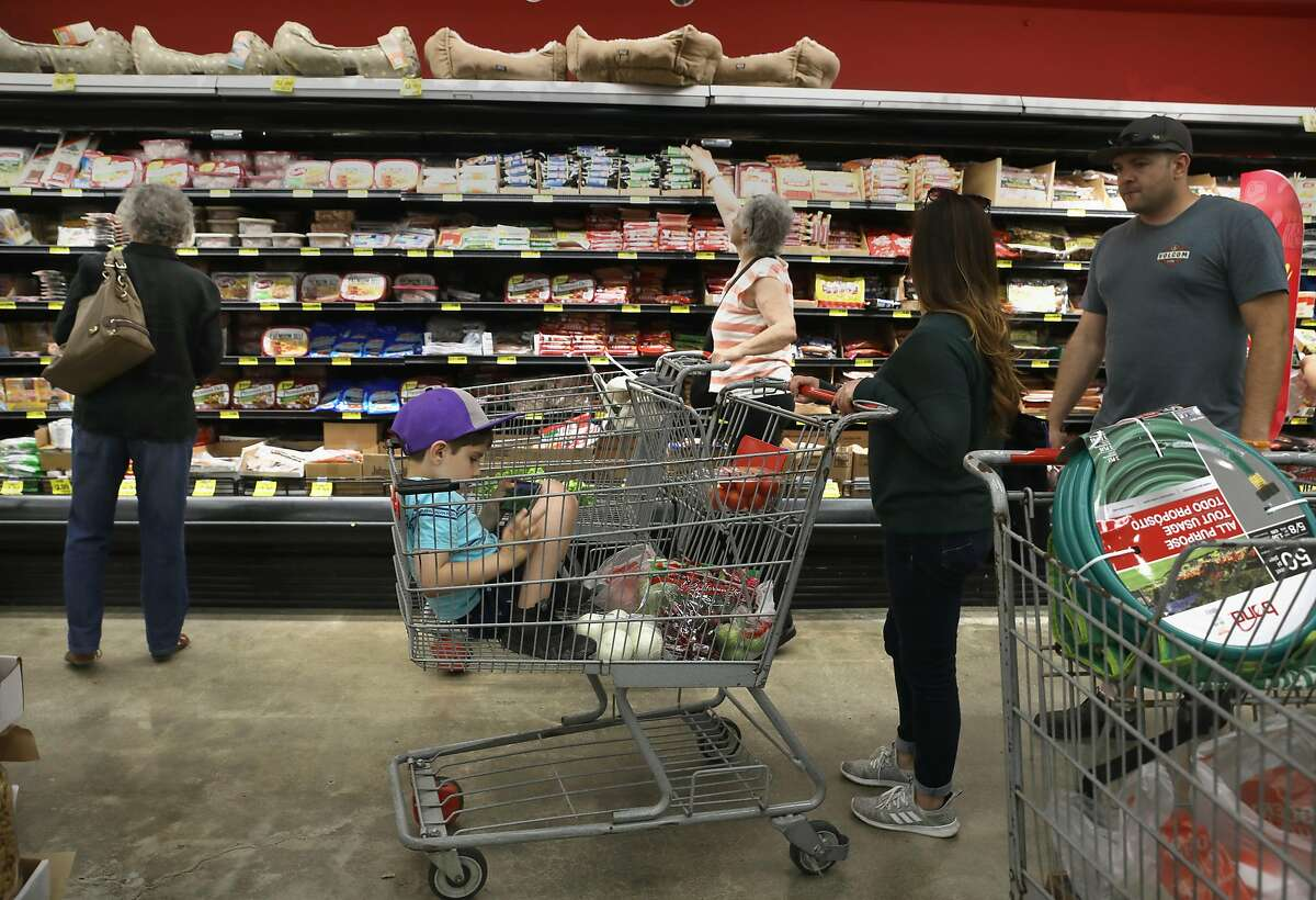 Susana Casillas (right) and her husband Thiago Alves (far right) shop as their six year old sits in their shopping cart at Grocery Outlet, a 73-year-old company with Bay Area roots on Monday, June 17, 2019, in Oakland, Calif. Grocery Outlet, the Emeryville discount chain is set to become a public company this Thursday, planning to raise as much as $275 million.
