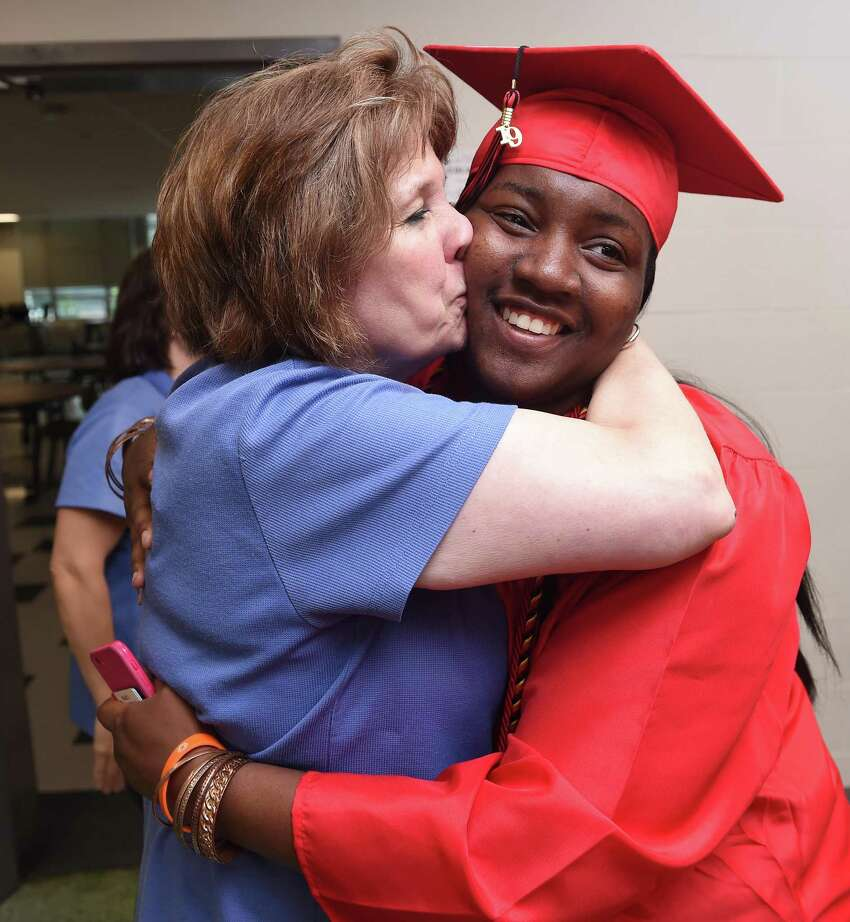 Cafeteria worker Joanne Hammill (left) gives a hug and kiss to Jayda Edmonds as the procession of graduates at Central High School in Bridgeport heads to gymnasium for graduation exercises on June 18, 2019.