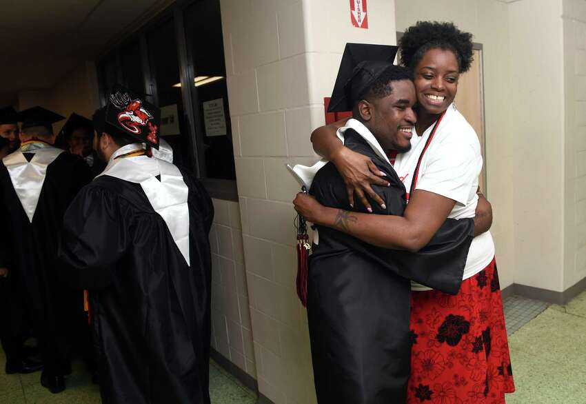 Kemoy Blair (center) gets a hug from his aunt, Olga Digsby, as graduates line a hallway at Central High School in Bridgeport before graduation exercises begin on June 18, 2019.
