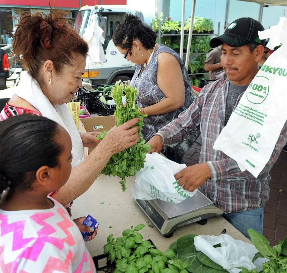 Rosa Azcona buys celantro from Jose Lopez at Smith Acres booth at the Citycenter Danbury Farmers' market Friday, July 10, 2015. Photo: Carol Kaliff / Hearst Connecticut Media / The News-Times