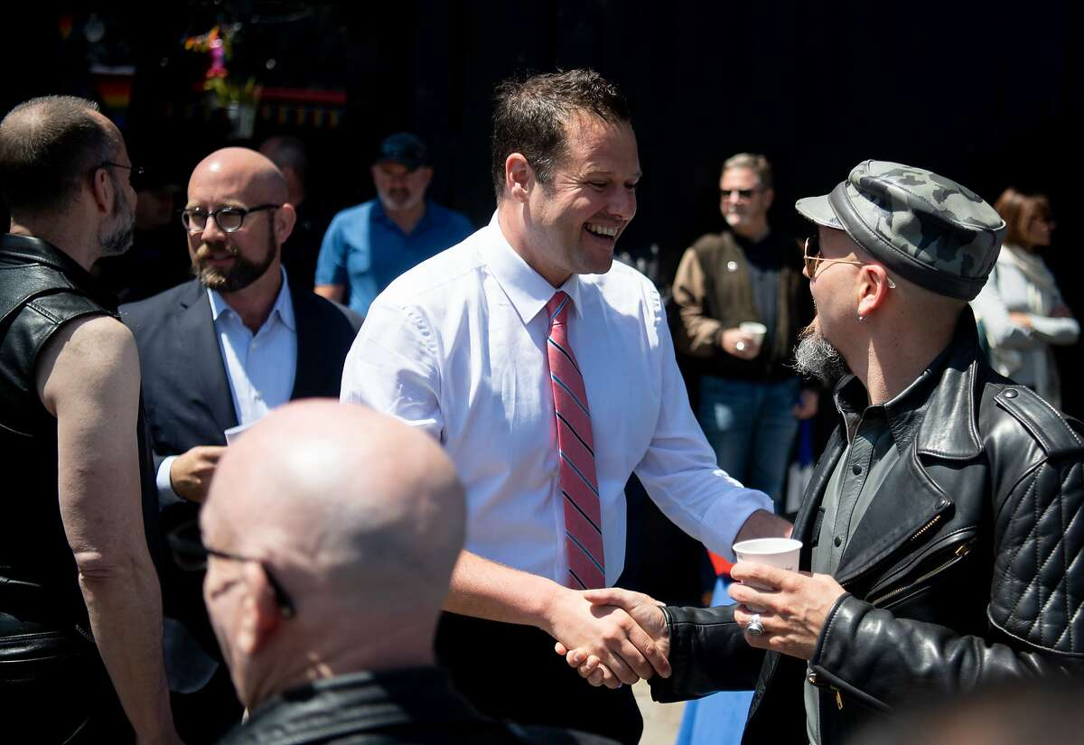 District 6 Supervisor Matt Haney (L) shakes hands with a leather-clad attendee at the groundbreaking of the world?•s first public plaza dedicated to the living commemoration of Leather Heritage at the SF Eagle Bar in San Francisco on Tuesday, June 18, 2019.