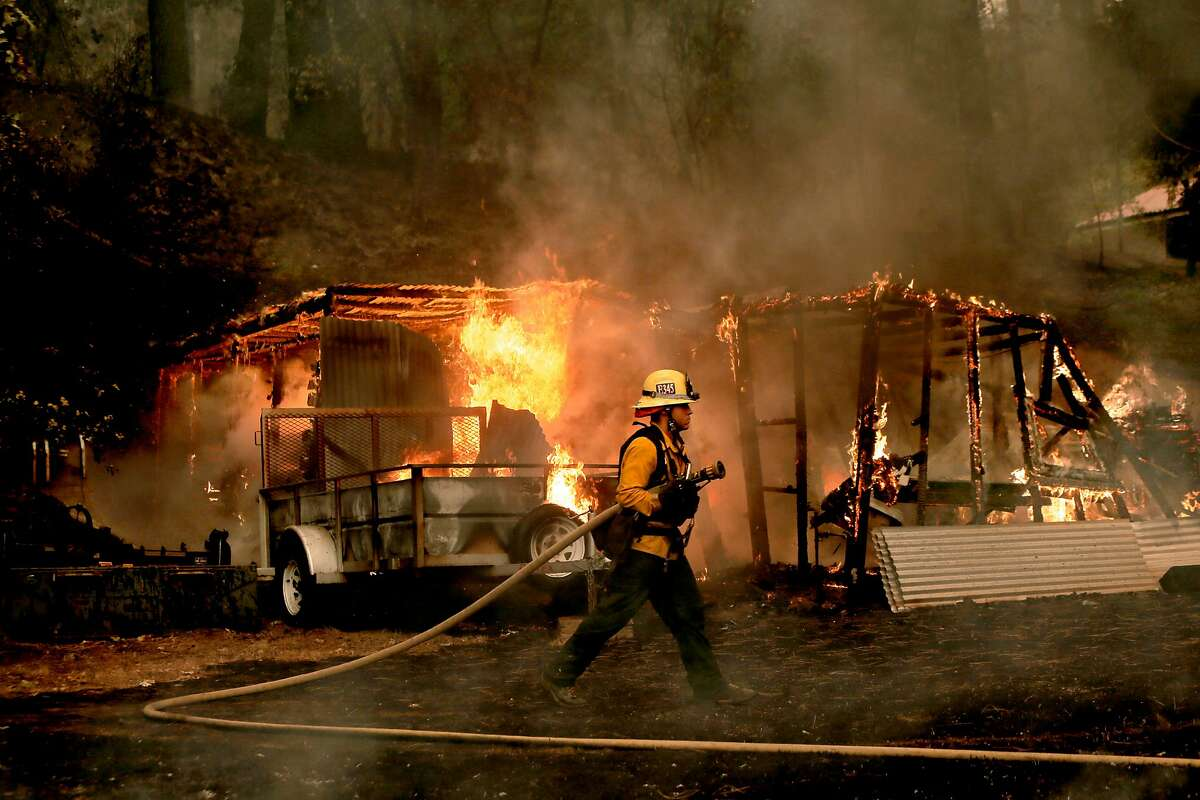 Firefighter Jarrett LaShure from Ventura Co. waits for the water to be turned on as he prepares to extinguish an out building along Sheep Ranch Road in Sheep Ranch, Calif, as the Butte Fire continues to burn on Sat. September 12, 2015.