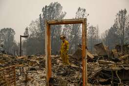 Paradise Firefighter Mike Rea surveys a property for remains at the Paradise Community Village Apartments following the Camp Fire in Paradise, California, on Tuesday, Nov. 13, 2018.