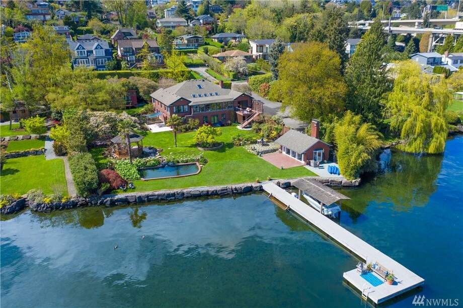 "This Lake Washington ""compound"" includes five bedrooms and five baths in its 6,242 square feet of space. It also includes 124 feet of shoreline, a private dock, a beach cabana and views of Mount Rainier. The home is for sale for $7.5 million. Photo: Photo Courtesy Luca Sforza, Lensit Studios"