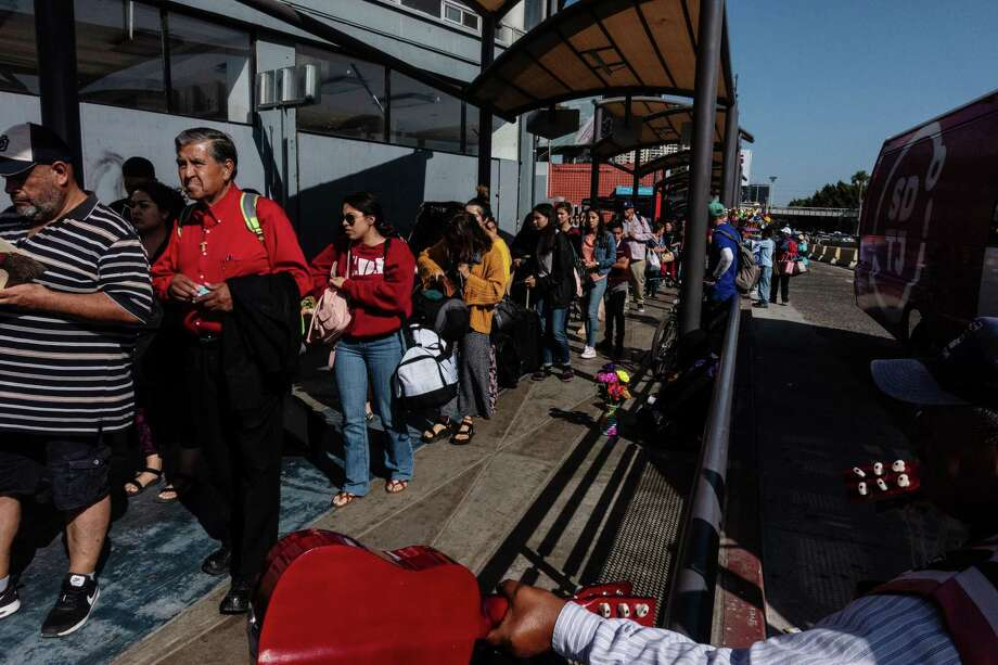 People wait in line at the San Ysidro port of entry in Tijuana, Mexico, on Sunday. President Donald Trump threat of tariffs on Mexico forced that country to agree to restrictions on Central American migrants trying to get to the U.S. Photo: Cesar Rodriguez /Bloomberg / © 2019 Bloomberg Finance LP