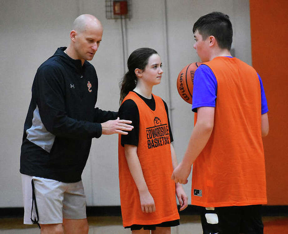 Edwardsville coach Dustin Battas runs through a drill Tuesday with two campers during the skills camp inside Lucco-Jackson Gymnasium. Photo: Matt Kamp/The Intelligencer