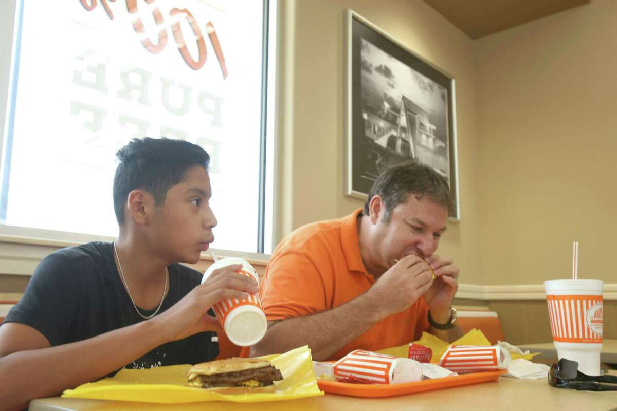 Father, Bill Long (right), and his son enjoy a hamburger and fries at the Whataburger off Silber Road in Houston, Tx Thursday, June 4, 2015. ( Dylan Aguilar / Houston Chronicle )