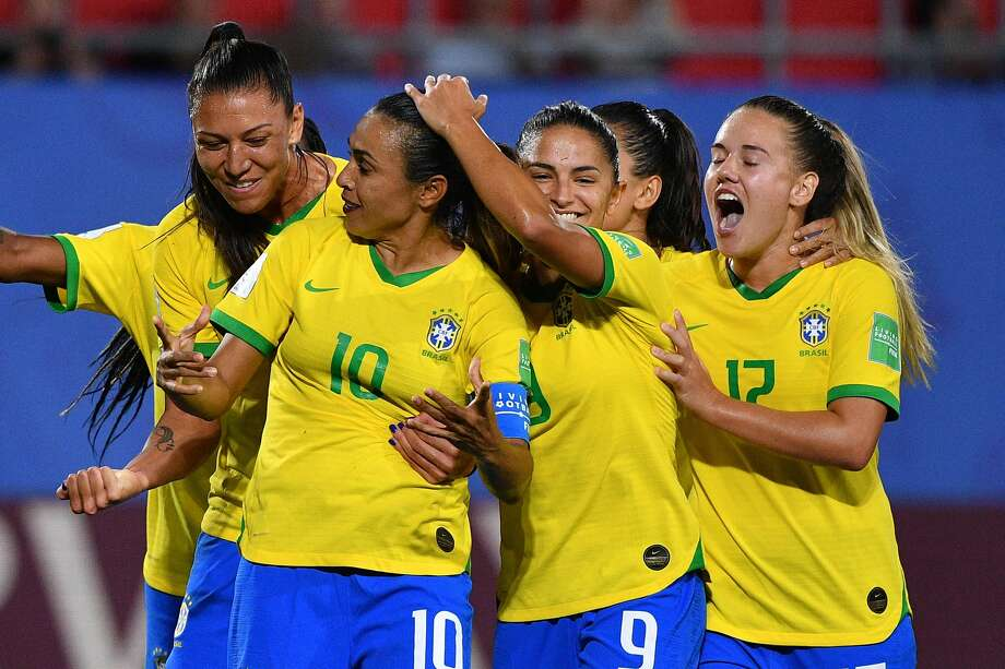 Brazil forward Marta (10) is congratulated by teammates after scoring her 17th World Cup goal, a record. Photo: Philippe Huguen / AFP / Getty Images