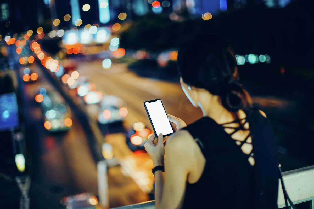 Rear view of woman using mobile phone in city against busy urban traffic during rush hour at night