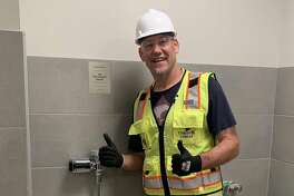 Tom Tolbert stands with the urinal honoring him at the Chase Center.