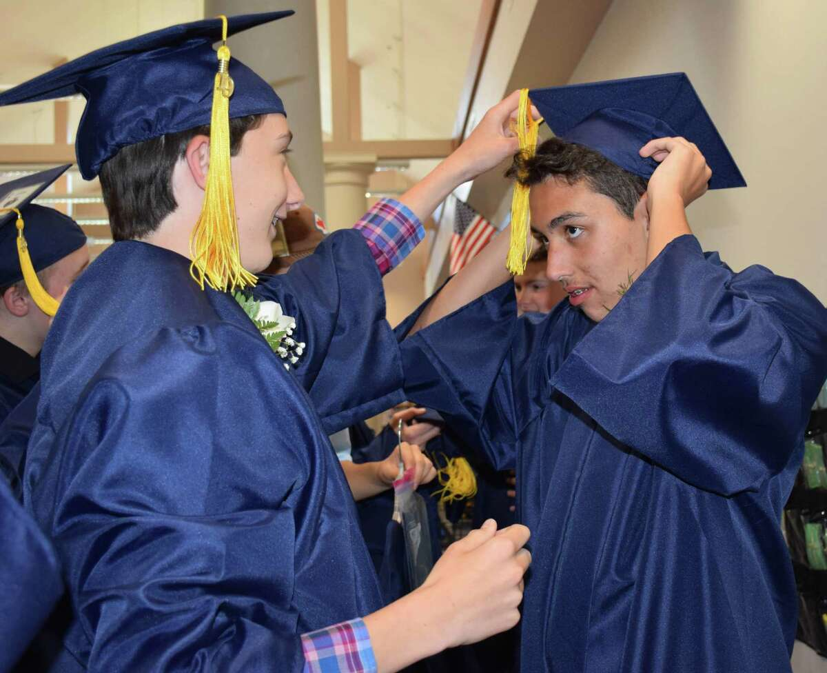 Trevor Hodges, left, helps James Philapakos place his cap on his head as students don their caps and gowns.