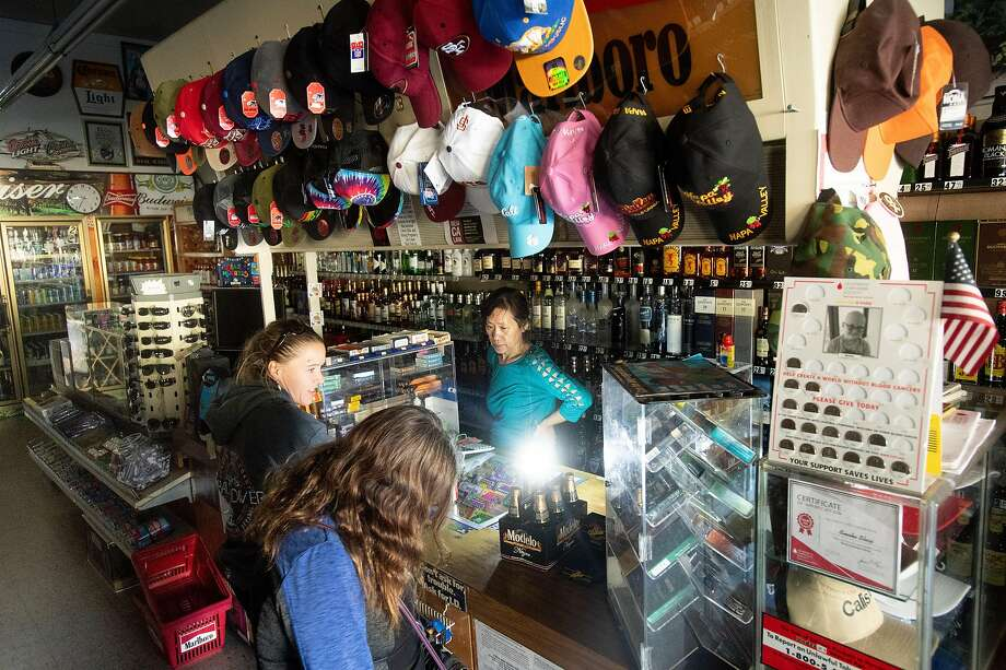 Victoria Um at the Calistoga Smoke Shop serves customers in the dark during a PG&E power shutoff a year after the Tubbs Fire. Most businesses in Calistoga closed after PG&E cut electric service in an effort to prevent fires amid red flag fire warnings in October 2018. Photo: Noah Berger / The Chronicle 2018