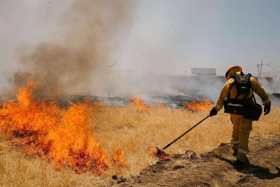 A firefighter uses a tool to spread a wall of flames during a controlled burn training in Tracy. Cal Fire has hired 60 people to do controlled burns, clear brush and thin forests near about 200 high fire-risk communities. Photo: Sarahbeth Maney / Special To The Chronicle