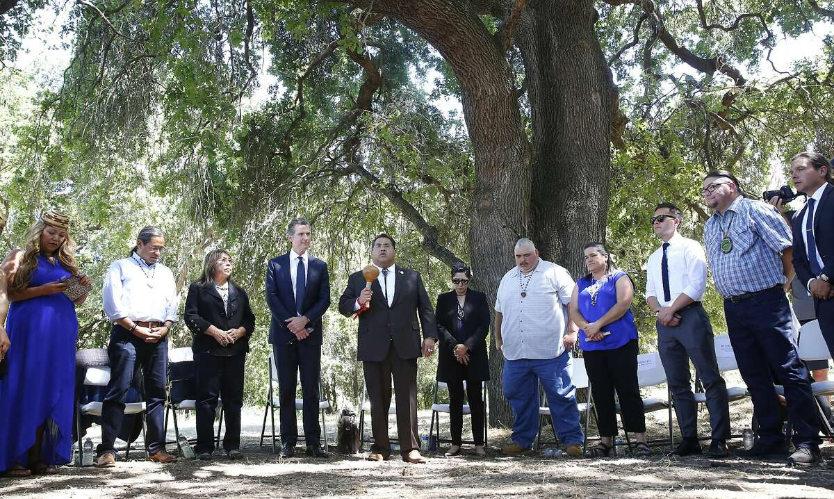 Assemblyman James Ramos, D-Highlands, of the San Manuel Band of Mission Indians, fifth from left, opens a meeting with tribal leaders from around the state, attended by Gov. Gavin Newsom, fourth from left, at the future site of the California Indian Heritage Center in West Sacramento, Calif., Tuesday, June 18, 2019. Newsom took the occasion to formally apologize to tribal leaders from around California for the violence, mistreatment and neglect inflicted on Native Americans throughout the state's history. (AP Photo/Rich Pedroncelli)