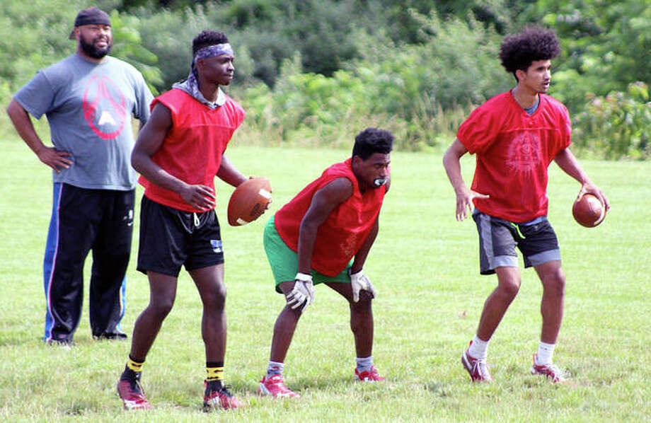Alton assistant coach Mel Sheppard keeps on eye on players (from left) Kavontay Samelton, Dasani Stewart and Andrew Jones during a drill Tuesday at Alton High School. Photo: Pete Hayes | The Telegraph
