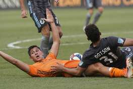 Houston Dynamo Ronaldo Pena looks for a call after he and Minnesota United FC Hassani Dotson tangle over ball during the first half of game at BBVA Stadium Tuesday, June 18, 2019, in Houston.