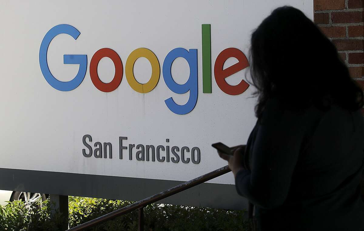 FILE - In this May 1, 2019, file photo, a woman walks past a Google sign in San Francisco. Google is making a $1 billion commitment to address the soaring price of housing in the San Francisco Bay Area, a problem that the internet company and its Silicon Valley peers helped create as the technology industry hired tens of thousands of high-paid workers. (AP Photo/Jeff Chiu, File)