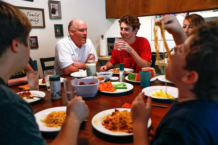 Loren Lighthall (center,left) chats at the dinner table with Lance Lighthall, 17 (center,right) during dinner a their temporary apartment in Chico, California, on Tuesday, May 21, 2019. The Lighthall's home was destroyed in the Camp Fire that decimated Paradise. The family of nine could not afford to stay in the Chico area and were forced to move to Modesto. Photo: Gabrielle Lurie / The Chronicle