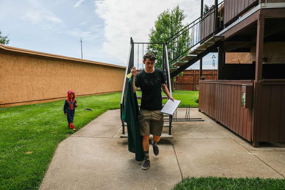 Paradise High School senior Lance Lighthall,17 walks to his car, carrying his cap and gown as his brother Peter,4 looks on just hours before graduation in Chico, California, on Thursday, June 6, 2019. Lance's home was destroyed in the Camp Fire that decimated Paradise midway through his senior year. His family of nine could not afford to stay in the Chico area and were forced to move to Modesto. Lance plans to attend BYU-Idaho in the Fall. Photo: Gabrielle Lurie / The Chronicle