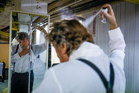 Actor Phil John spray paints his hair white as he prepares for rehearsals for the Nutcracker in Oroville, California, on Thursday, Jan. 17, 2019.