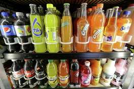 FILE - This Sept. 21, 2016 file photo shows soft drink and soda bottles displayed in a refrigerator at El Ahorro market in San Francisco. The California Legislature is expected to vote to prohibit local governments from creating new taxes on soda on Thursday, June 28, 2018. In exchange, the beverage industry has agreed to drop a ballot measure that would have made it much harder for cities and counties to raise taxes. (AP Photo/Jeff Chiu, File)