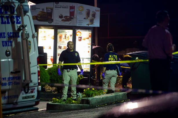 FILE -- Police investigate a drive-thru where mobster Sylvestre Zottola was assassinated, in the Bronx, Oct. 4, 2018. The mastermind of the killing, federal prosecutors now say, was actually a member of a family even closer to Zottola - his own son.