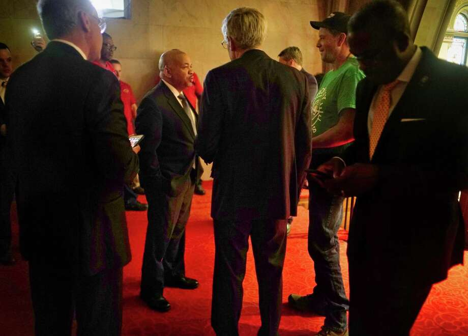 Assembly Speaker Carl Heastie, background left, talks with Rick Zimmerman, center, of Zimmerman and Associates, and Tim Stanton, second from right, owner of Stanton's Feura Farm, in the gallery above the Assembly during debate of the Farmworker Fair Labor Practices Act on Wednesday, June 19, 2019, in Albany, N.Y. Stanton is against the Farmworker Act in its current form and talked with Speaker Heastie about that.  (Paul Buckowski/Times Union) Photo: Paul Buckowski, Albany Times Union / (Paul Buckowski/Times Union)