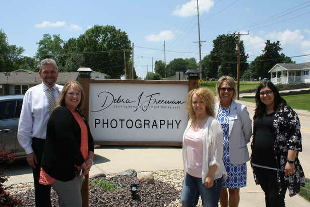 Officials from Catching Memories Photography stand next to the business's signage.