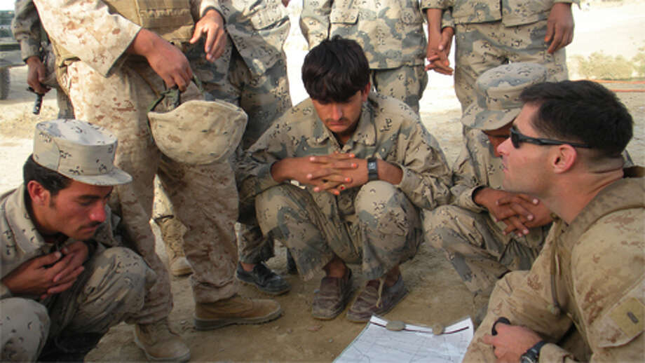 Marien 1st Lt. Derek J. Claiborne, right, reviews a map with the Afghan Border Police.