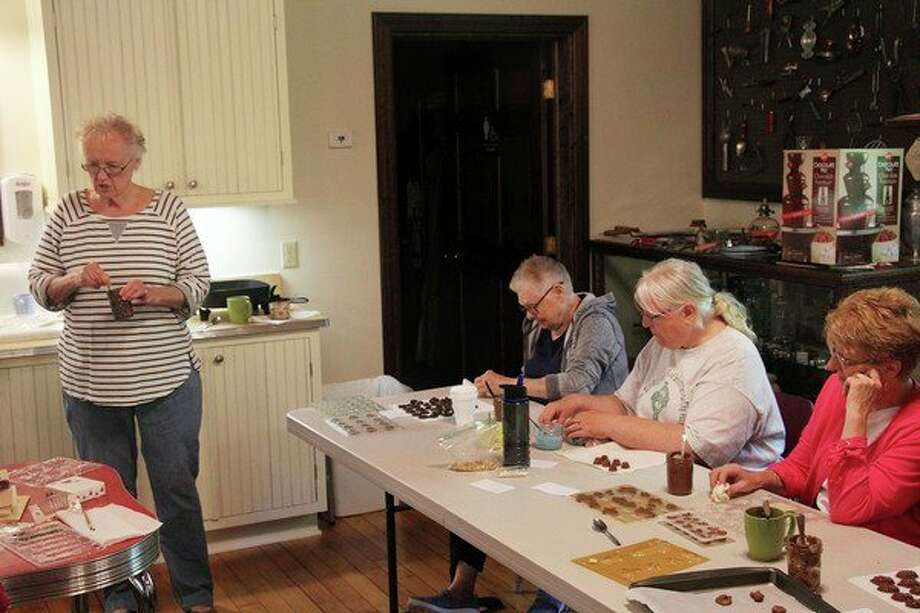 Pat Letwin, standing, leads a molded chocolate candy class at the Port Austin History Center. She said making chocolates and selling them is a relatively easy way to start a small business. (Seth Stapleton/Huron Daily Tribune)