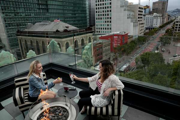 Jackie O'Reilly, right, and Haley Null, left, share drinks overlooking Market Street at Charmaine's, the rooftop bar and lounge at the Proper Hotel in San Francisco, Calif., on Thursday, May 9, 2019.