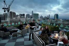 Guests enjoy drings overlooking Market Street at Charmaine's, the rooftop bar and lounge at the Proper Hotel in San Francisco, Calif., on Thursday, May 9, 2019.