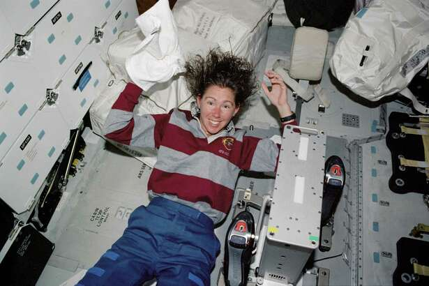 Sandy Magnus washes her hair aboard the space shuttle Atlantis in 2002.