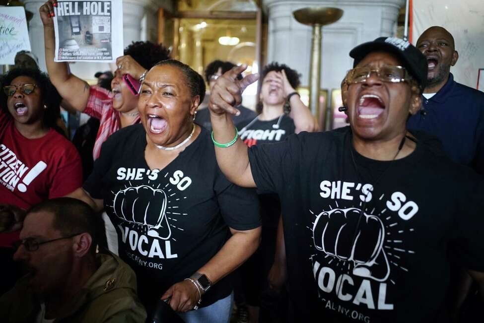Kim Smith, left, of Rochester, and Jovada Senhouse, of the Bronx, both members of Vocal New York, chant,