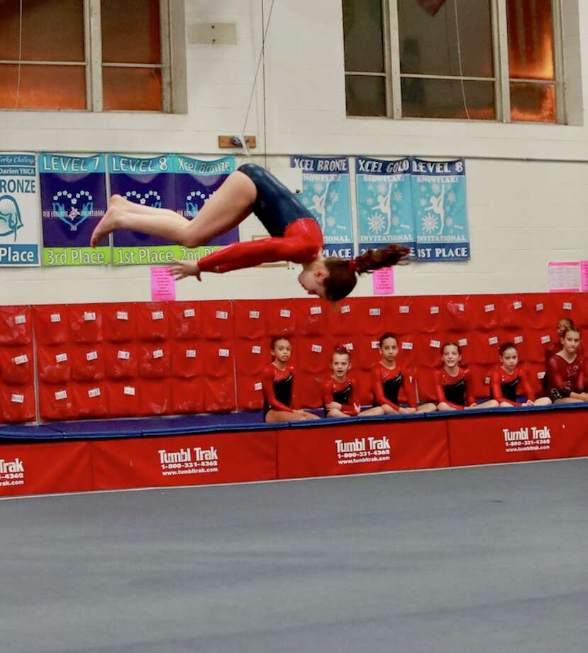 With her teammates cheering her on, Darien YMCA Level 6 gymnast Anna Altier flipped to a huge 9.4 score to win the floor title at the New England Invitational.