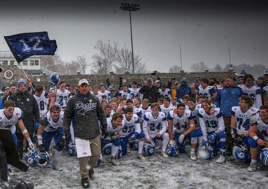 Coach Rob Trifone steps forward to accept the Class LL title plaque with champs chomping at the bit for a touch at Stamford on Saturday. Courtesy Darien Athletic Foundation / (c)Mark Maybell
