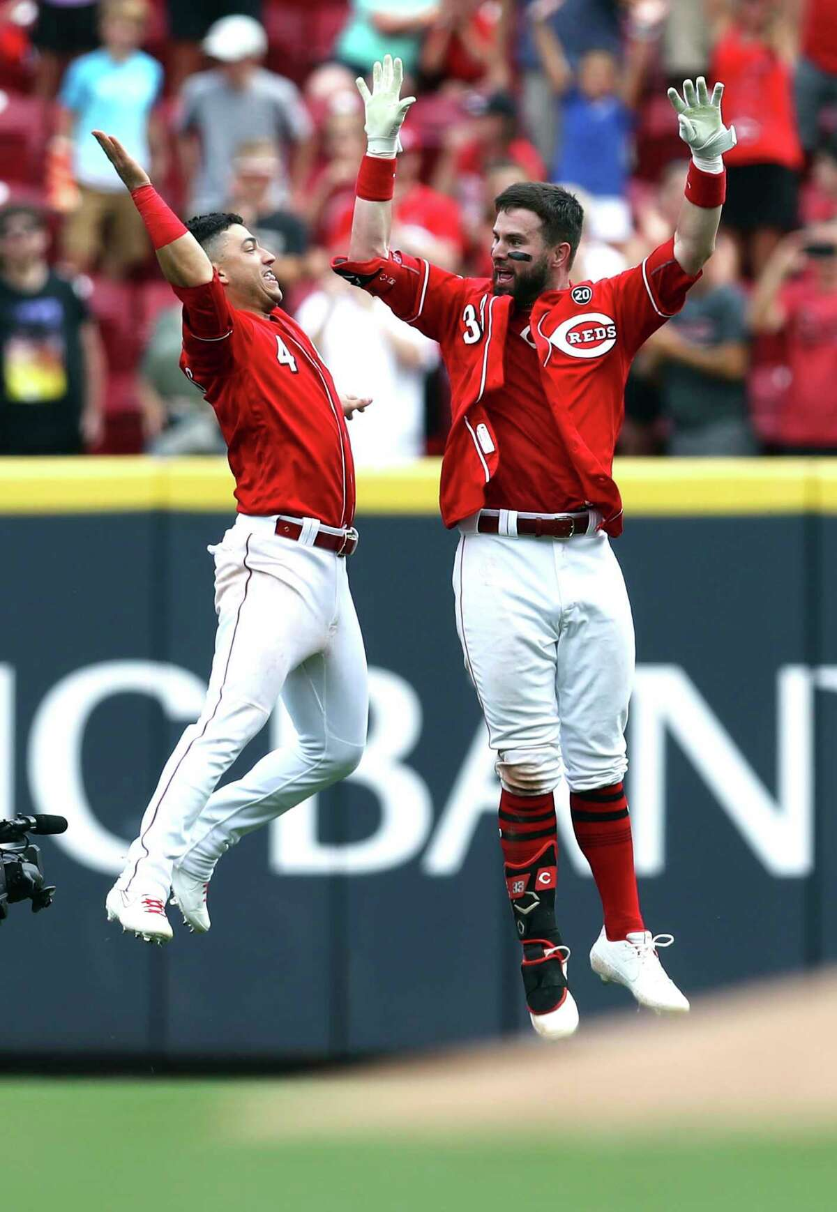 Cincinnati Reds' Jesse Winker, right, celebrates with Jose Iglesias, left, after hitting the game-winning RBI-single in the ninth inning of a baseball game against the Houston Astros, Wednesday, June 19, 2019, in Cincinnati. (AP Photo/Aaron Doster)