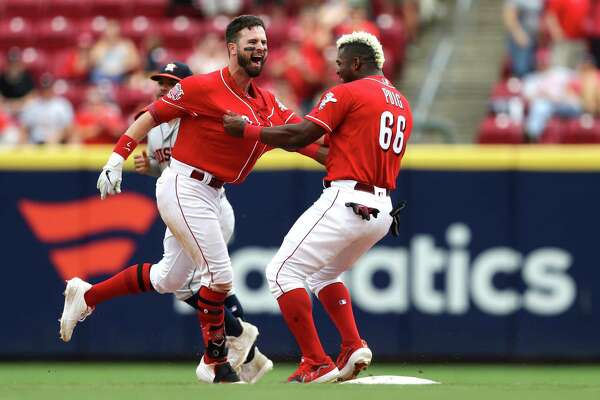 Cincinnati Reds' Jesse Winker, left, celebrates with Yasiel Puig, right, after hitting the game-winning RBI-single in the ninth inning of a baseball game against the Houston Astros, Wednesday, June 19, 2019, in Cincinnati. (AP Photo/Aaron Doster)