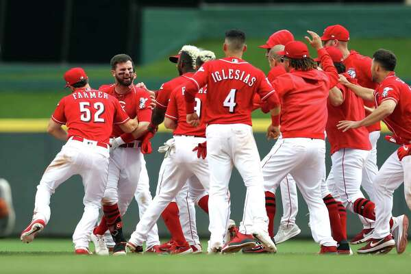 Cincinnati Reds' Jesse Winker, left, celebrates with teammates after hitting the game-winning RBI-single in the ninth inning of a baseball game against the Houston Astros, Wednesday, June 19, 2019, in Cincinnati. (AP Photo/Aaron Doster)