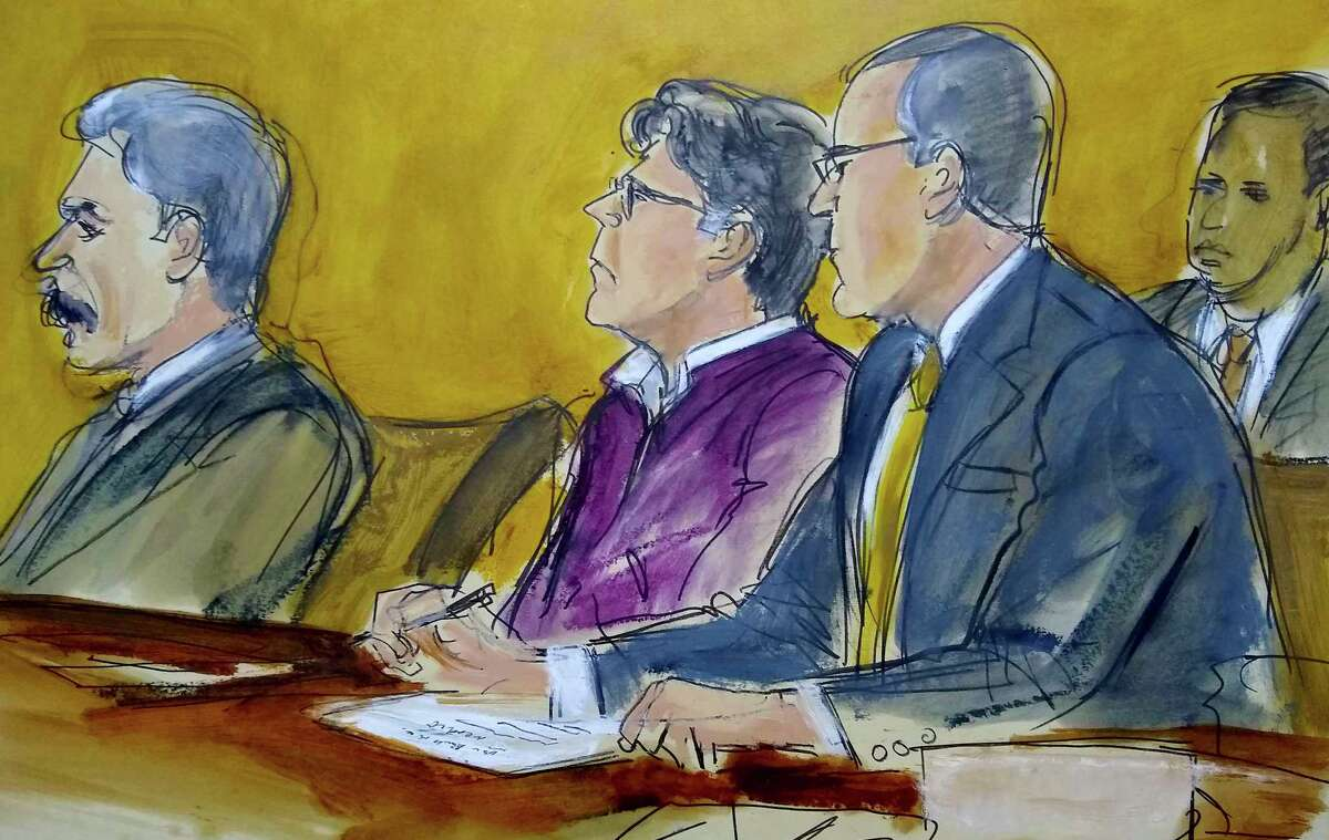 In this courtroom drawing, defendant Keith Raniere, center, sits at the defense table with his attorneys Paul DerOhannesian, left and Marc Agnifilo, as the jury foreperson reads the guilty verdict in his sex trafficking trial in New York, Wednesday, June 19, 2019. The former leader of a cult-like self-help group was convicted Wednesday of manipulating his female followers through shame and humiliation and turning them into what prosecutors call his sex slaves. The man at rear is a Deputy US Marshal.