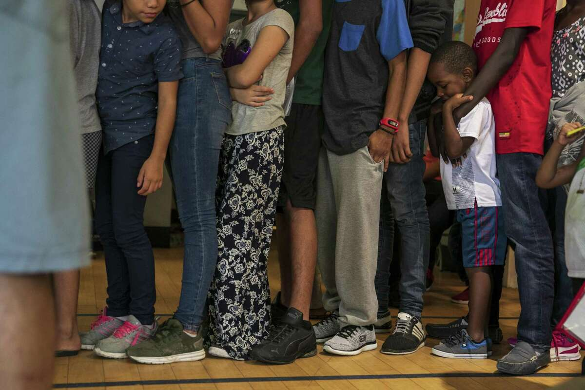 Migrants line up for a meal inside a shelter in downtown San Antonio on June 14.