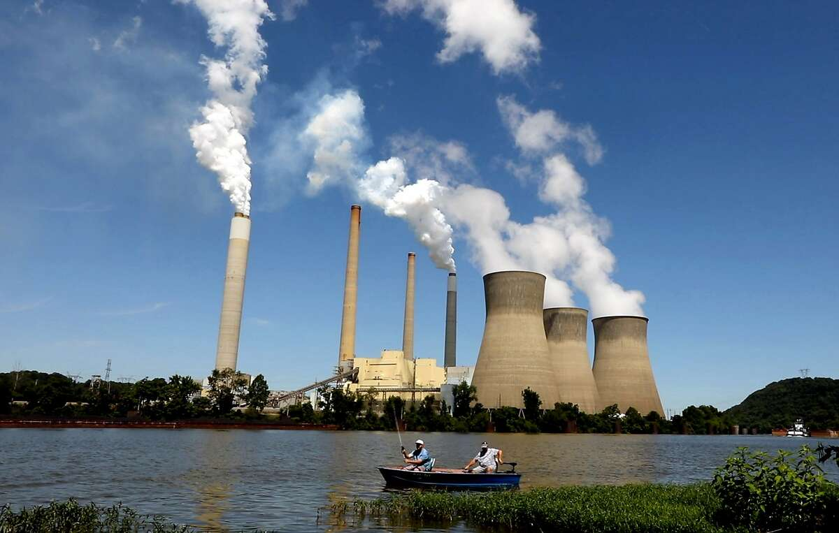 Fishermen drift by the John E. Amos coal-fired power plant operating on the banks of the Kanawha River near Winfield, W.V. (Carolyn Cole/Los Angeles Times/TNS)