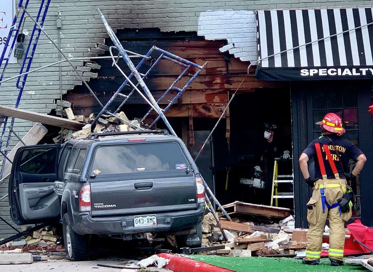 Houston firefights work the scene where truck slammed into the side of Carmelita's Cuisine at the corner of 11th Street and Studewood in the Heights in June 19, 2019.