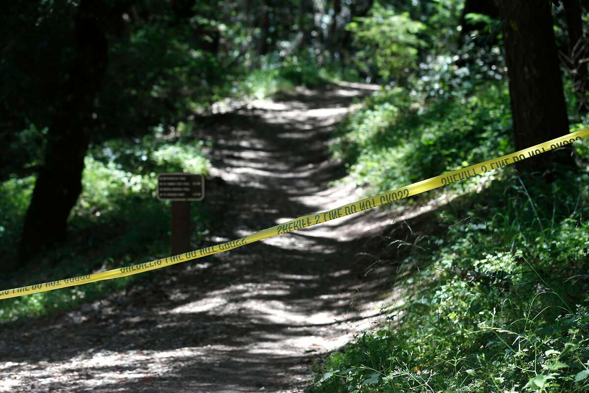 Yellow crime scene tape remains stretched across a trailhead at El Corte de Madera Creek Open Space Preserve after police detectives finish their investigation of two stabbing homicides on Skyline Boulevard west of Woodside, Calif. on Wednesday, June 19, 2019.